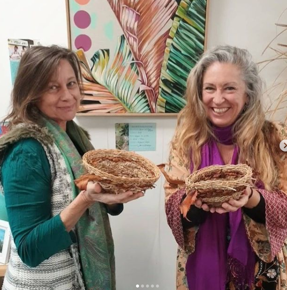 WEaving workshop participants holding baskets they made at the Island Arts Gallery WEaving workshop