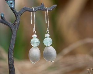 earrings by Amber Vicum with nicker nut native seeds and pale green beads